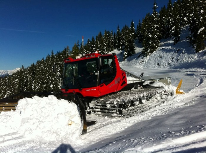 A piste basher packing down early October snow on  the Hauser Kaibling